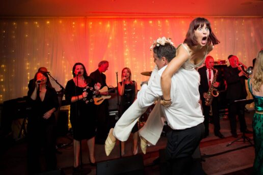bridesmaid picked up by man on the dance floor at courtyard hall
