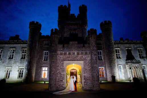 evening shot of the wedding couple by the entrance to hensol castle
