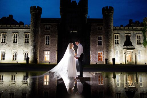 evening picture of bride and groom in front of hensol castle