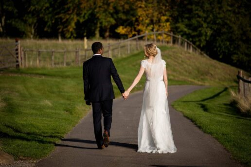 brdie and groom walk holding hands at kingscote barn