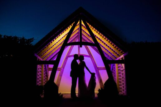 silhouette of the kissing couple inside the oak linhay at kingscote barn