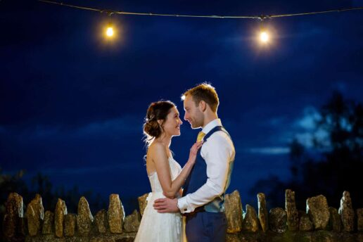wedding couple embracing each other during twilight with two light hanging behind them at kingscote barn