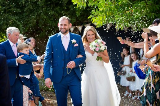 guests throwing confetti at bride and groom after the ceremony at brympton house in somerset
