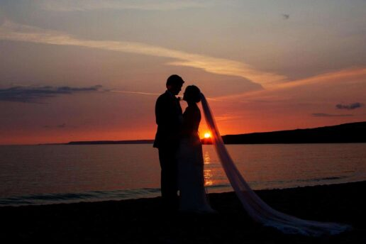 silhouette of wedding couple with setting sun behind them at oxwich bay in gower