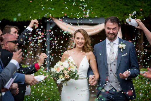 wedding couple walking through the guests throwing confetti at St. Tewdricks in Chepstow