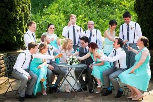 bridal party making toast sitting around bride and groom at coombe lodge in somerset