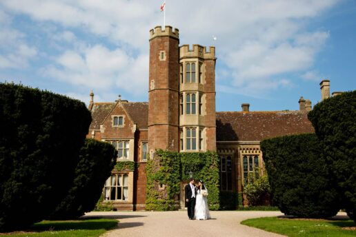wedding couple walking in front of St Audries Park wedding venue in Somerset