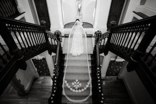 bride showing her long wedding veil at the stairs at st audries park in somerset