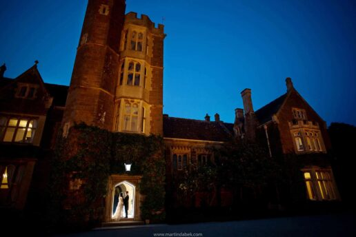 twilight shot of wedding couple at the entrance to st audries house