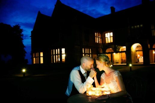 couple sitting by the table at twilight light with the candles with coombe lodge wedding venue in the background