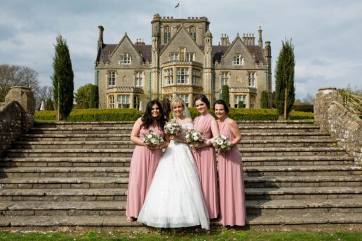 bridesmaids standing on the steps in front of de vere tortworth court