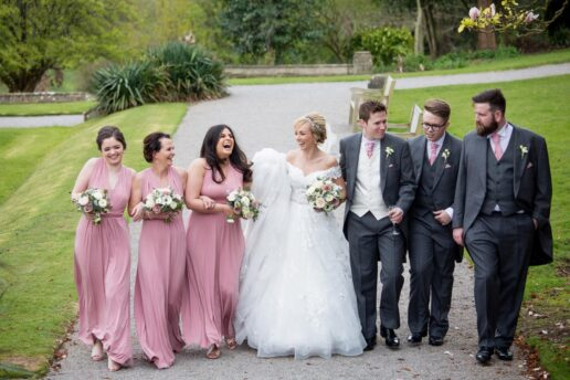 bridal party walking together in the gardens at de vere tortworth court