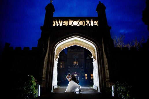 wedding couple kissing each other in front of welcome gate at de vere tortworth court