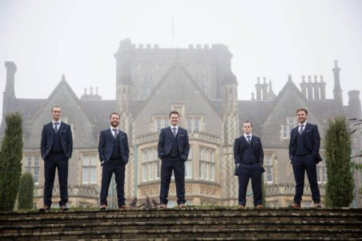 groomsmen standing on top of the steps with tortworth court behind them