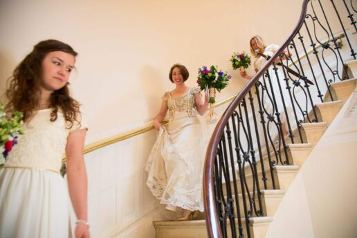 bride and her bridesmaids walking down the spiral staircase at eastington park