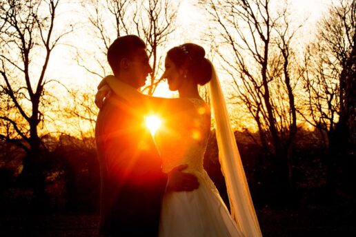 bride and groom facing each other with the setting sun between them