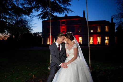 evening portrait of bride and groom kissing on the swing with eastington park in the background
