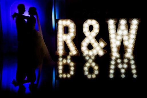 bride and groom facing each other with their first initial light letters next to them