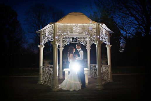 evening shot of the wedding couple facing each other inside the pergola at eastington park