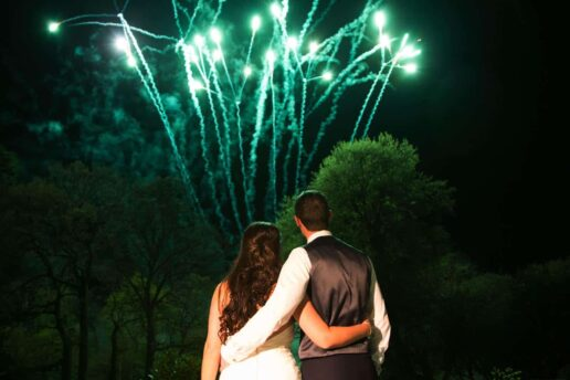 wedding couple embrecing each other and looking at the fireworks dispaly at eastington park