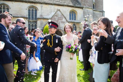 confetti thrown on the wedding couple in front of church of St Michael and All Angels in Eastington in Gloucestershire