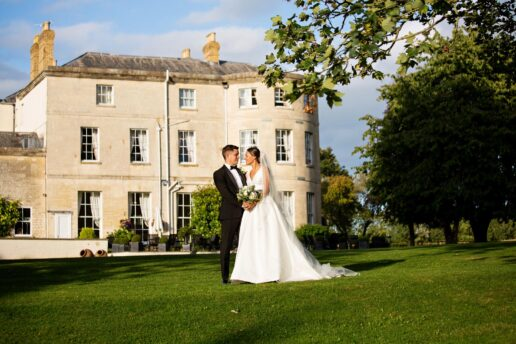 wedding couple in front of eastington park in gloucestershire