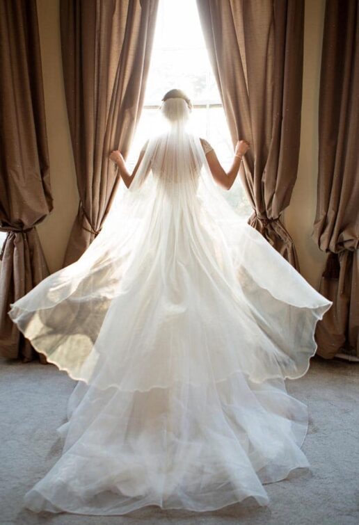 bride looking through the window with the sunlight shining through her veil at honeymoon suite at eastington park