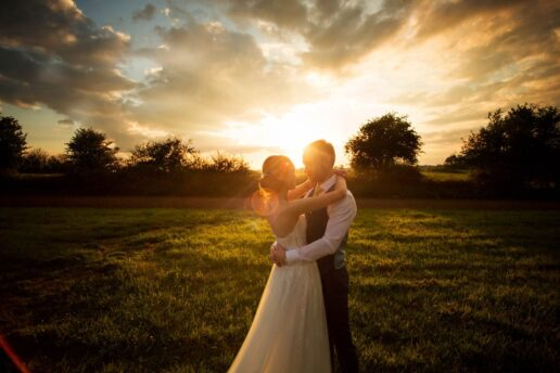 bride and groom embracing on the field at winkworth farm with a sun setting behind them