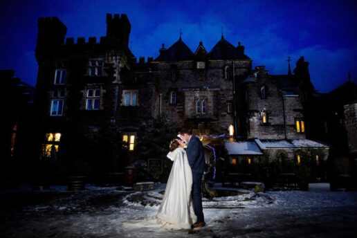 wedding couple kissing in snow in front of craig-y-nos castle in wales