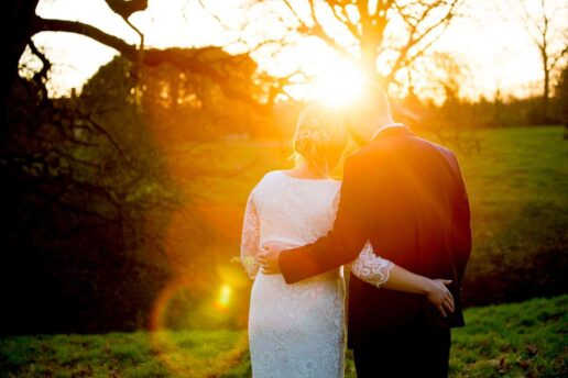 wedding couple embracing with sun setting between them