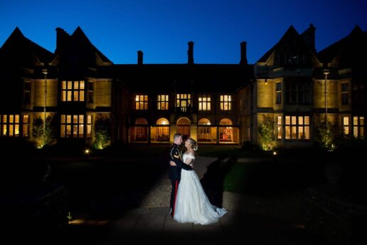 wedding couple holding each other in front of coombe lodge during the twilight hour