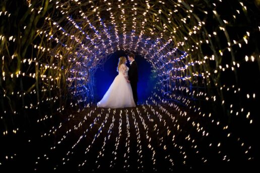 WEDDING COUPLE FACING EACH OTHER INSIDE THE TUNEL OF FAIRY LIGHTS
