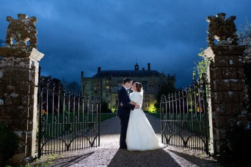 twilight picture taken in winter of the wedding couple embracing each other in front of the gate with brympton house in the background