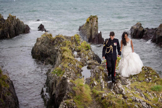 wedding couple walking on the sea rocks with the sea behind them