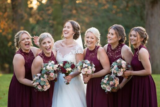 bride and bridesmaids in red dresses laughing at clearwell castle