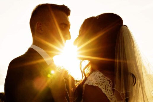 wedding couple facing each other with the setting sun behind them at clearwell castle in gloucestershire