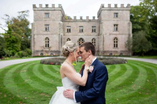 wedding couple embracing each other in front of clearwell castle wedding venue in the forest of dean