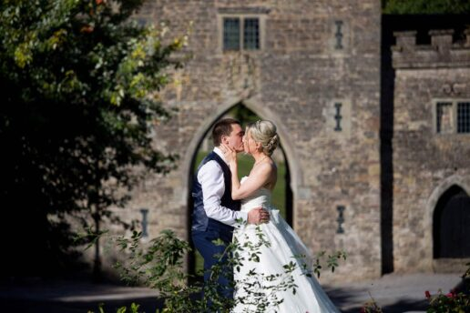 wedding couple kissing with a clearwell castle gateway behind them