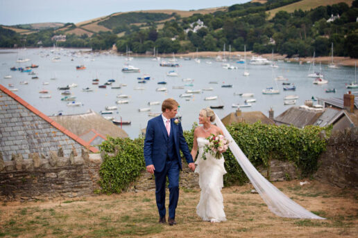 wedding couple walking holding hands with Guernsey bay with sailing boats behind them