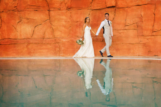 wedding couple walking holding hands in front of the pool which create the reflection of them and the orange rock behind them