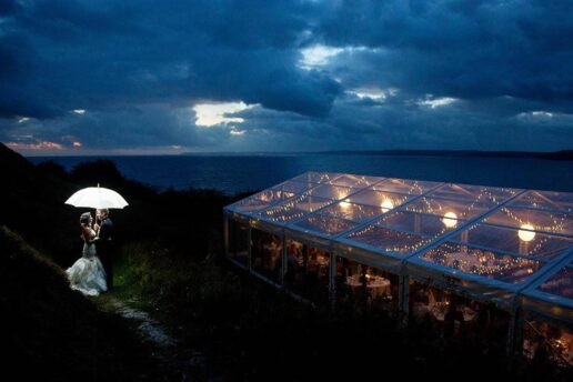 wedding couple under the backlight umbrella at the twilight with a dramatic sky and sea behing them and lit marquee on the side