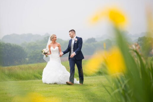 wedding couple walking holding hands at quantock lakes wedding venue