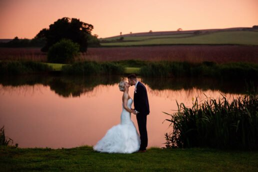 wedding couple standing and kissing in front of the lake with a red sky behind them at quantock lakes in somerset