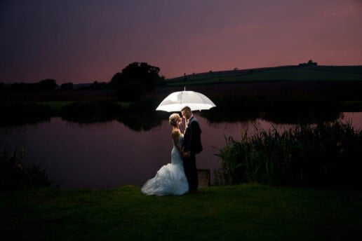 twilight picture of wedding couple standing under the lit white umbrella in front of the lake at quantock lakes