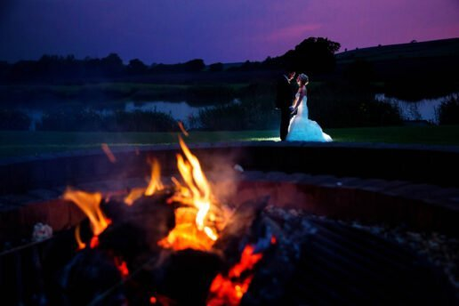 night shot of the lit fire pit with a wedding couple in the distance