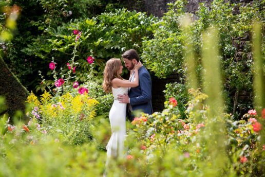 wedding couple embracing each other in the samares manor botanical garden on jersey island
