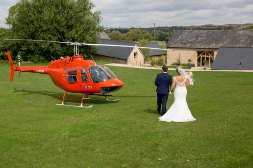 wedding couple waking on the field towards the barn at upcote in the cotswolds with a red helicopter standing next to them
