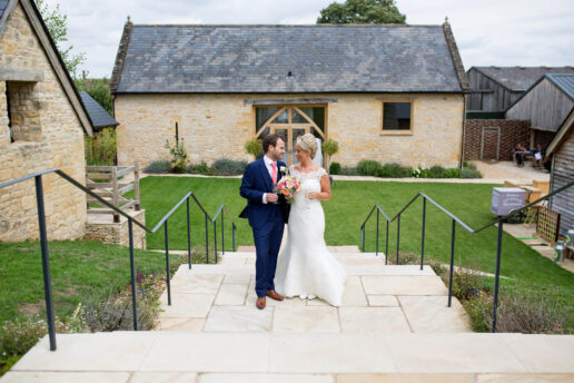 wedding couple standing on the stairs with the threshing barn at barn at upcote behind them