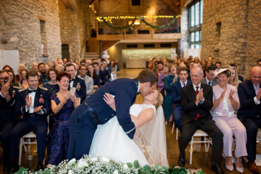 groom kissing the bride at the ceremony at priston mill in somerset