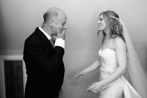father of the bride crying looking looking at her daughter in wedding dress for the first time